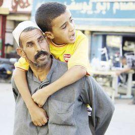 «عطية» حاملاً ابنه المريض: «كان نفسى هو اللى يشيلنى»