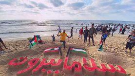 """رسام البحر.. محمد ينحت عبارة """"سلاما لبيروت"""" على شاطئ غزة: نتضامن معهم"""