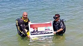 «ابن الشهيد منسي» يرفع علم مصر بصورة والده والرئيس بأعماق المتوسط