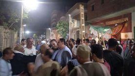 أنصار مرشح يرفعون السلالم الخشبية في مسيرة انتخابية ببني سويف