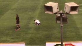 أحد عمال ستاد الكلية الحربية يرمم أرضية الملعب بين شوطي مباراة الأهلي