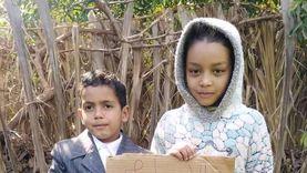 طفلا «شهيد الأرض» بنجع حمادي يطالبان بالقصاص بلافتة