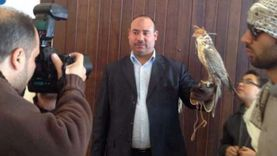"""رواد """"فيس بوك"""" بقنا يتداولون صورة مرشح يحمل صقرًا بـ100 ألف دينار"""