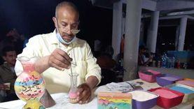 يرسم على الزجاج بالرمال الملونة.. «أحمد» فنان يجذب مصطافي مطروح (صور)