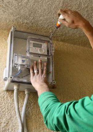احد العاملين بالكهرباء خلال تركيب العدادات