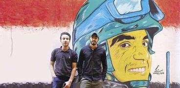 «أحمد» وصديقه «محمود» بجوار اللوحة