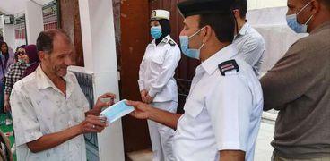 أحد أفراد الشرطة يعطي كمامة مجانية لأحد الناخبين