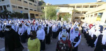 الطالبات يلتزمن بارتداء الكمامات الطبية أثناء طابور الصباح لمواجهة كورونا