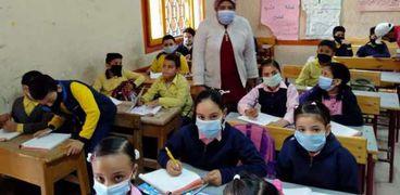 الطلاب يرتدون الكمامات الطبية داخل الفصول الدراسية مع عودة الدراسة بالمدارس