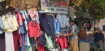 «أحمد» يعرض ملابسه مجاناً فى الشارع