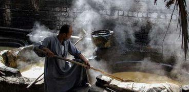 عامل ينقل العسل من حوض لآخر
