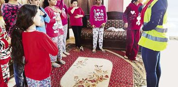 أخصائية اجتماعية أثناء تدريب الفتيات داخل إحدى دور الأيتام