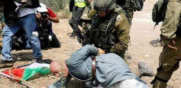 جندي إسرائيلي يعتدي على مسن فلسطيني