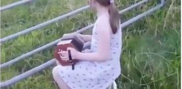 طفلة موهوبة تتجمع حولها الأبقار لتستمتع بعزفها للموسيقى