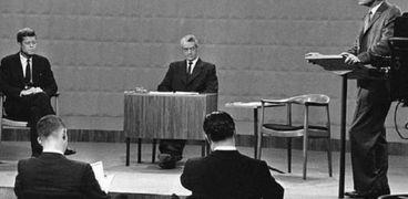 نيكسون واقفا وكينيدي جالسا إلى أقصى اليسار