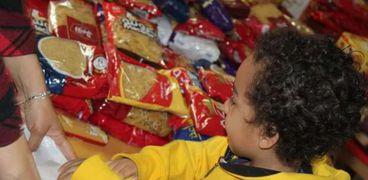 لغرز قيم المشاركة.. أطفال يساهموا في توزيع شنط رمضان: ونعم التربية