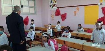 طلاب يرتدون واقي الوجه داخل فصل دراسي