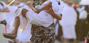 رجل أمن سعودي يحمل حاجا مسنا