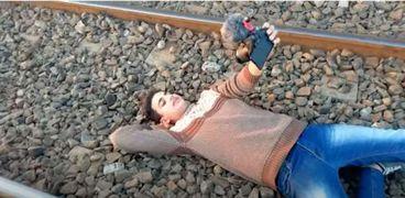 لقطة من الفيديو أثناء نوم شاب على أحد قضبان السكة الحديد