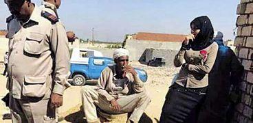 قوات الشرطة مع «منى» أثناء فتح الحفرة التى تم دفن الضحية وابنتها بها