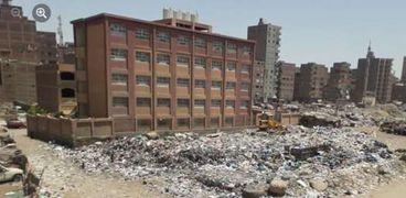 حيوانات ميتة ومخلفات مصانع بجانب إحدى المدارس