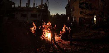 فلسطينيون يجلسون حول نار بينما يقضون ليلتهم بالقرب من منازلهم المدمرة في قطاع غزة