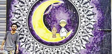 أحمد شعبان بجوار الجدارية التى رسمها
