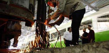أحد العمال أثناء إصلاح عربة ترام داخل الورش