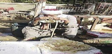 «عم أحمد» أثناء تنظيف «الممبار»