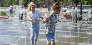 فتاتان روسيتان تحاولان الهرب من درجات الحرارة المرتفعة في روسيا