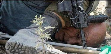 """""""فلويد"""" جديد.. جندي إسرائيلي يضغط بركبته على عنق فلسطيني (صور)"""
