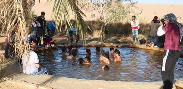 زوار سيوة يستمتعون بعين المياه الساخنة في منطقة بئر واحد السياحية الشهيرة
