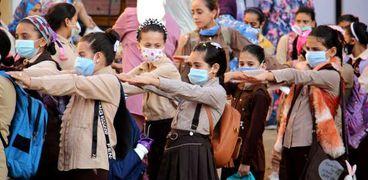 التلاميذ يرتدون الكمامات الطبية أثناء طابور المدرسة في غول أيام العام الدراسي الجديد