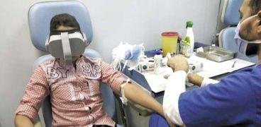 طفل مريض أثناء سحب عينة دم مرتدياً نظارة «VR»