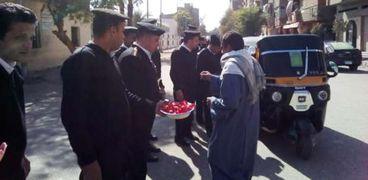 رجال الأمن يوزعون الشيكولاتة احتفالا بعيد الشرطة في أسوان