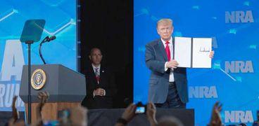 """الرئيس الأمريكي دونالد ترامب يظهر أمرا موقِعايرفض معاهدة تجارة الأسلحة لعام 2013 في الاجتماع السنوي للجمعية الوطنية للبنادق في """"إنديانابوليس"""""""