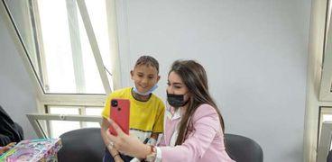 ياسمين صبري تلتقط «سيلفي» مع طفل بمستشفى أبوالريش