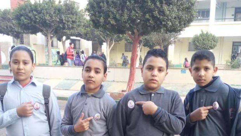 """طلاب يلصقون """"بادج كودك"""" على ملابس مدرستهم"""