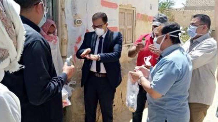 وكيل وزارة الصحة بمطروح خلال توزيعه ادوية للمخالطين بمنازلهم بقرية بهى الدين بسيوة