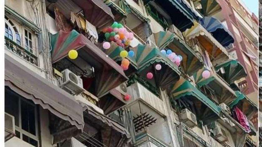 احدى السيدات تلقى البالونات على المارة