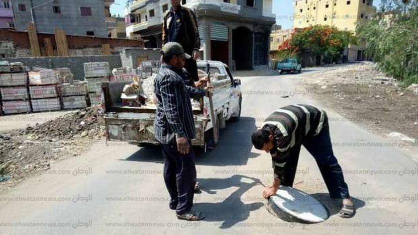 عمال الصرف الصحي خلال الكشف علي اغطيه البالوعات