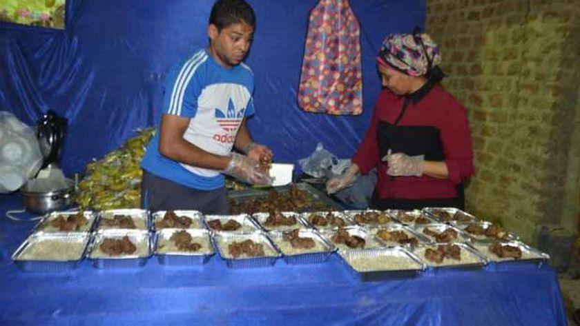 المتطوعون أثناء تجهيز الوجبات لتوزيعها على الصائمين اليوم