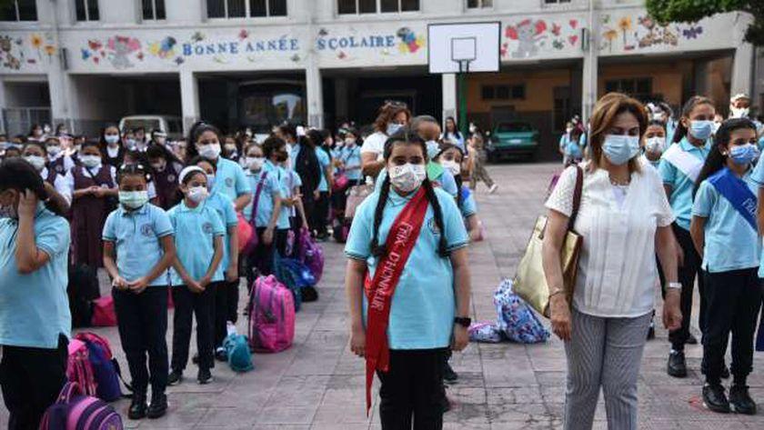 التلاميذ يلتزمون بارتداء الكمامات الطبية بسبب كورونا أثناء الطابور الصباحي