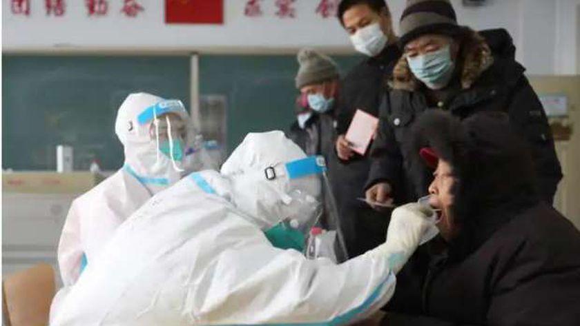 طبيب صيني يجري مسحة للحلق لأحد مرضى فيروس كورونا