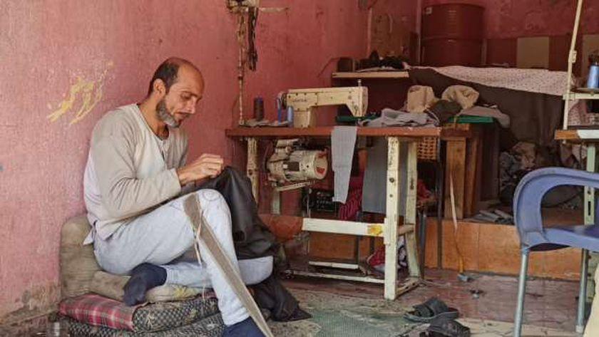 أبو وجيه يجلس في محل صناعة الجلاليب