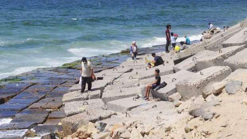 بالصور : سور وصخور كورنيش الإسكندرية ملجأ للهروب من الموجه الحرة