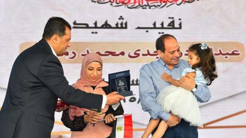 السيسي يحمل ابنة الشهيد