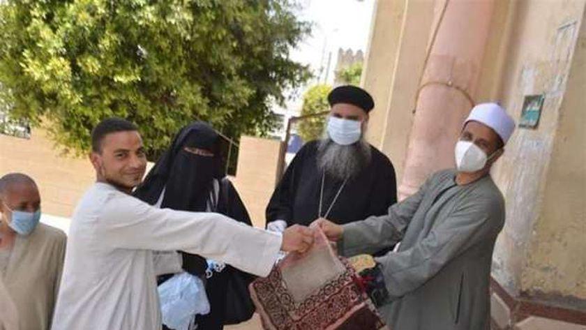 راعي كنيسة  الأم دولاجي بإسنا يوزع سجاد صلاة على المصلين