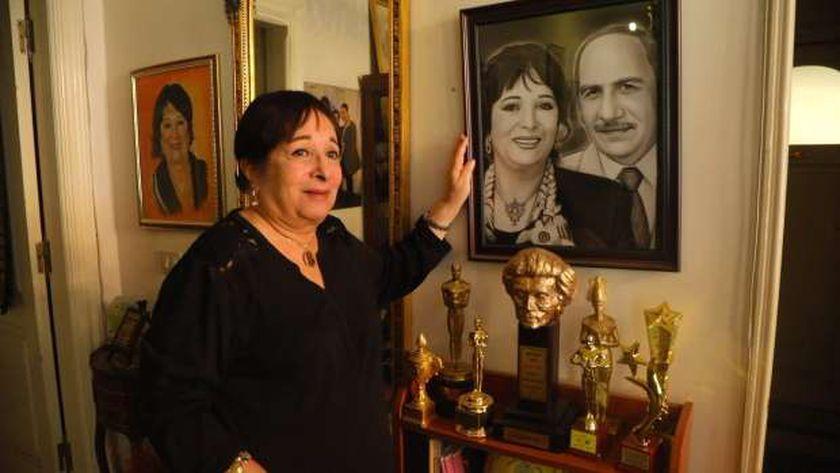الفنانة سميرة عبدالعزيز في منزلها أمام صورة تجمعها وزوجها الراحل محفوظ عبدالرحمن