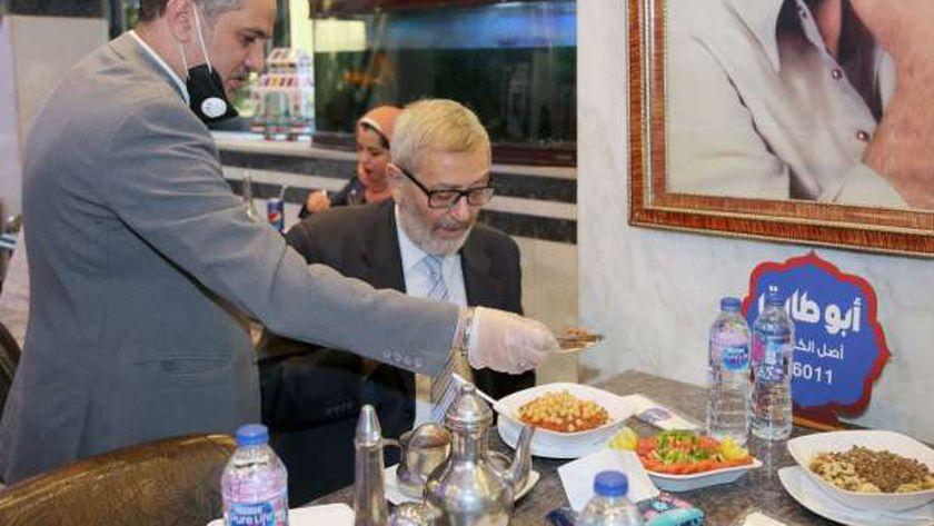 سفير ألبانيا بالقاهرة إدوارد سولو أثناء تناوله الكشرى فى وسط البلد